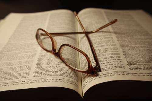Reading Glasses atop Pages of Open Dictionary Book