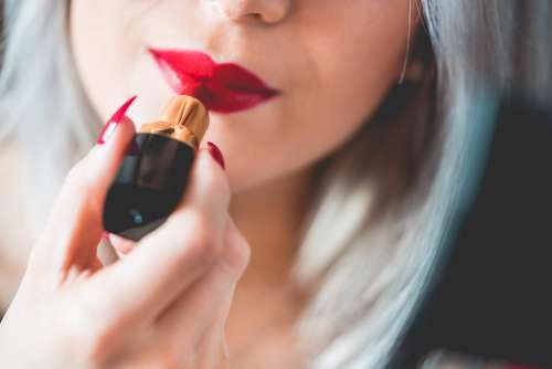 Young & Smiling Woman Applying Red Lipstick