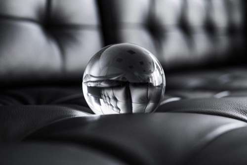 Big Glass Crystal Ball on Black Leather Sofa