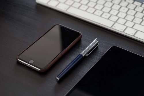 Black iPhone on Black Office Desk