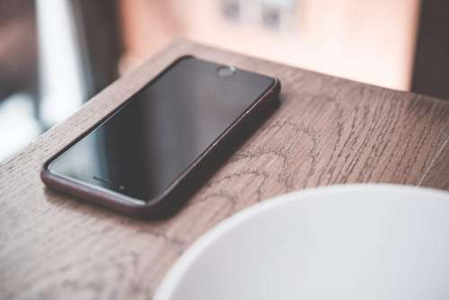 Black Smartphone on Wooden Table in Café