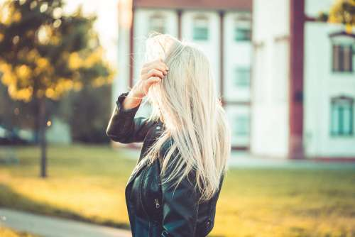 Blonde Woman Playing with Hair Against Sun