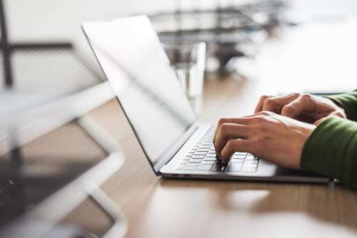 Business Copywriter Typing on His Modern Laptop