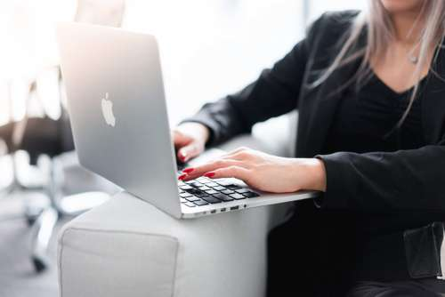 Business Woman Using Her Laptop on a Sofa