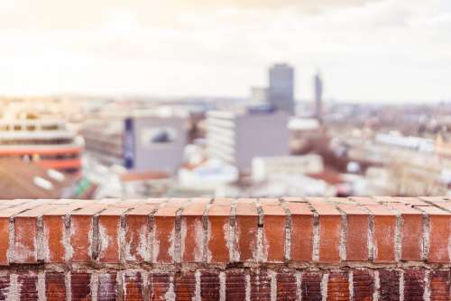 Empty Brick Wall with Blurred City View Background
