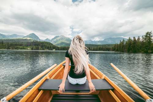 Young Blonde Woman Enjoying a Rowing Boat