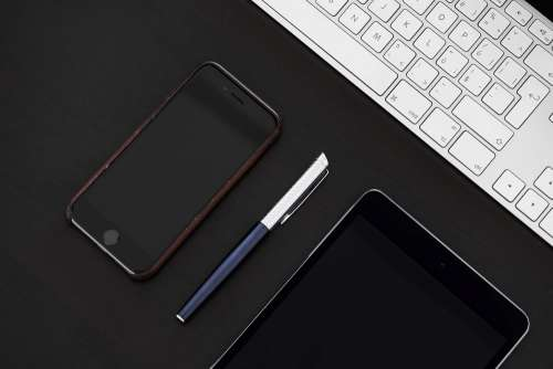 Smartphone with Pen on Office Desk From Above
