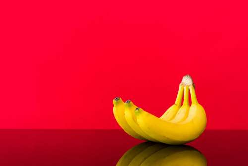 Fresh Bananas on Glossy Table and Red Background