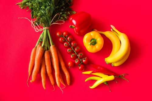 Fresh Fruits and Vegetables on Red Background Still Life