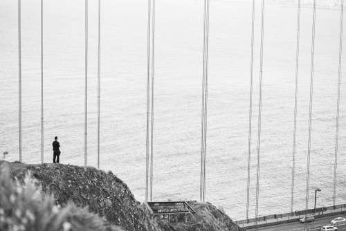 Man Stands at The Edge of The Cliff Near The Golden Gate Bridge