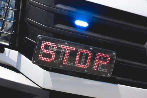 Police Flashing Light and STOP Sign on Car