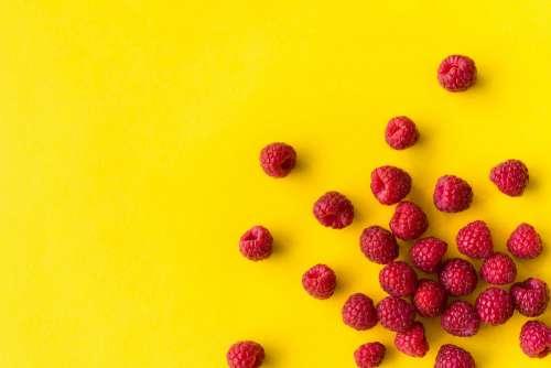 Raspberries on Flat Yellow Background
