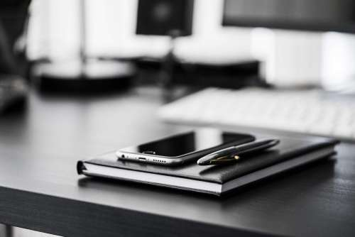 Smartphone, Diary and Silver Pen on Black Workspace Desk