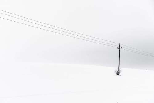 Snow Covered Hill and an Old Power Line Minimalistic