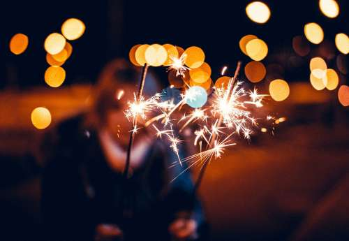 Woman Holding Sparklers in Hands