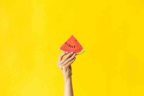 Slice of Watermelon in Woman Hand on Bright Yellow Background