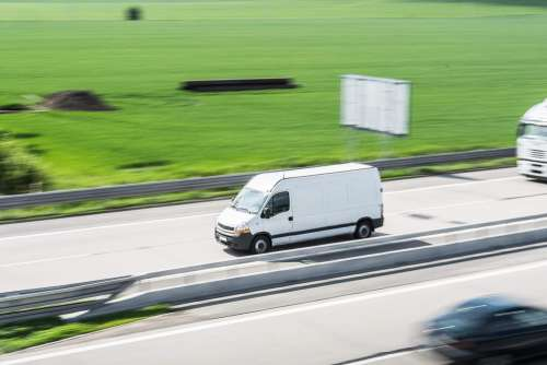 White Delivery Van in Motion Driving on Highway