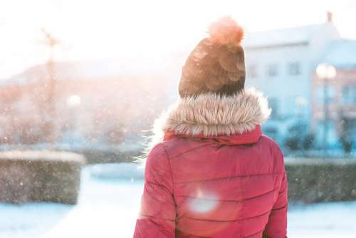Woman Standing in Snowfall while Sun is Shining