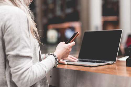 Woman Using Her Smartphone While Working Remotely on Laptop