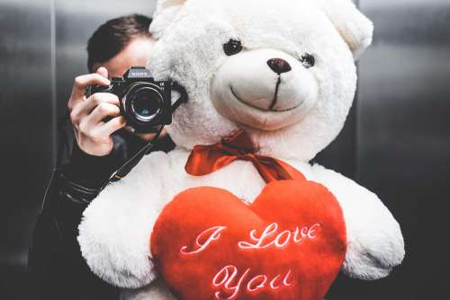 Young Man Taking Selfie with Big Teddy Bear for His Girlfriend in Elevator