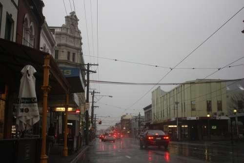 Rain Street Shops Wet Car Tram Lines