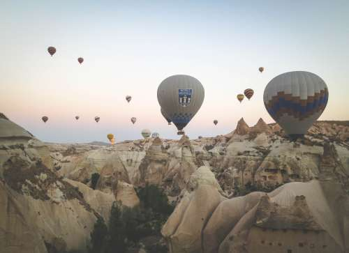 A wave of balloons emerge above the fairy chimneys of Cappadocia, Turkey.