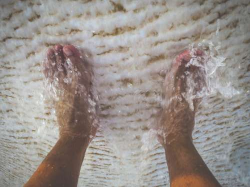 Water washes over his feet in thetravertine pools.