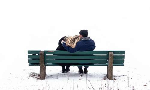 A Couple Cuddles On A Bench In The Snow Photo