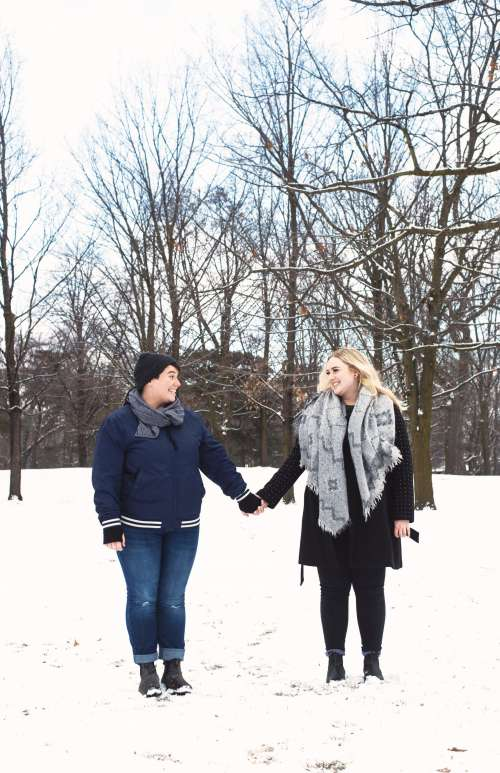 A Couple Hold Hands While Walking Through The Snow Photo