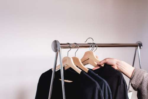 A Hand Removes A Sweater From A Clothing Rack Photo