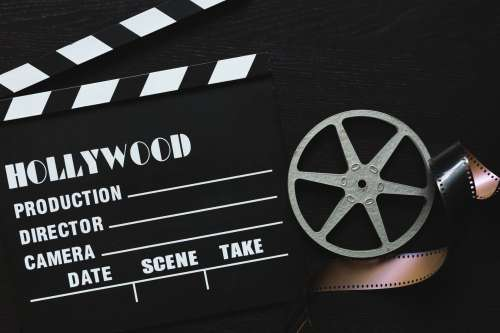 A Movie Clapper Board, Film Roll And Sprocket Wheel Photo