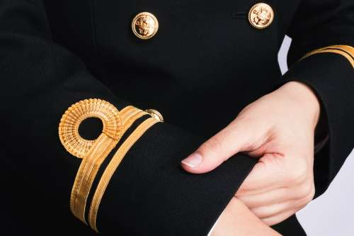 A Person Adjusts The Cuffs On Their Uniform Photo
