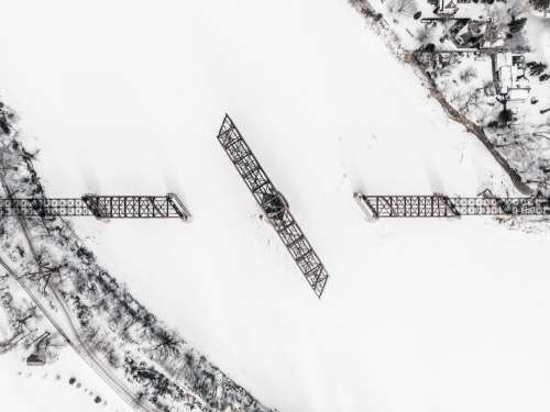 A Railway Swing Bridge On A Frozen River Covered In Snow Photo