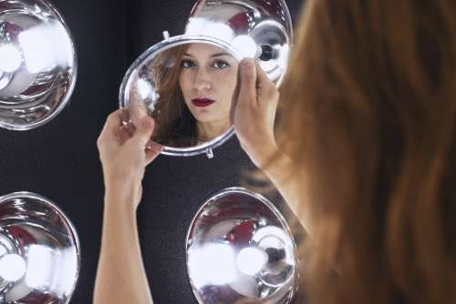 A Woman Is Holding A Mirror Reflecting Her Face To The Camera Photo