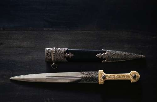 An Ornate Dagger And Sheath On A Wooden Table Photo