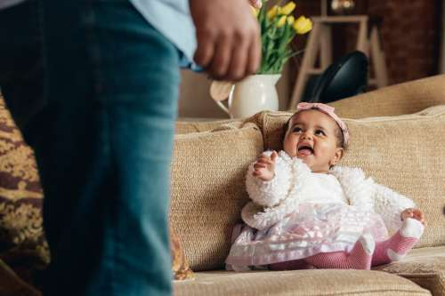 Baby Girl On Couch Lookingat Dad Smiling Photo