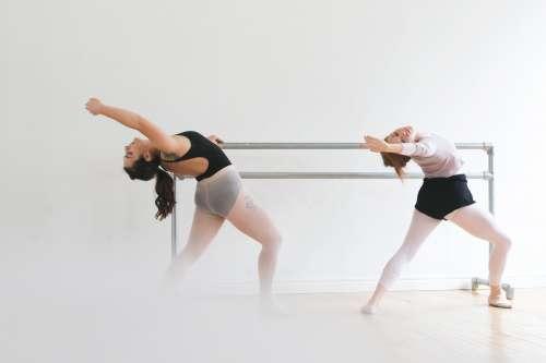 Ballet Dancers Warm Up At Bar Photo