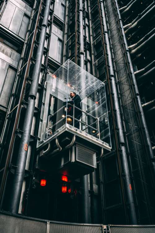 Businessman In Glass Elevator Going Up Photo