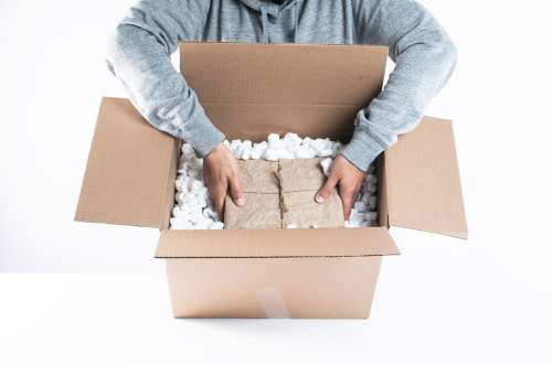 Carefully Placing A Package Into Packing Peanuts Photo