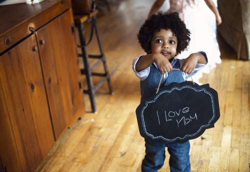 Child With I Love Mom Sign Photo