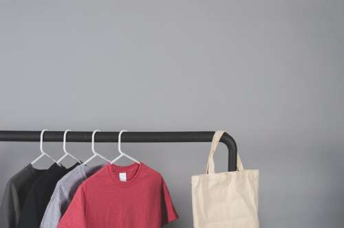 Clothes Rail Beside Gray Wall Photo
