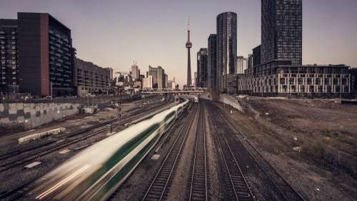 Commuter Train Speeds Past In City Photo