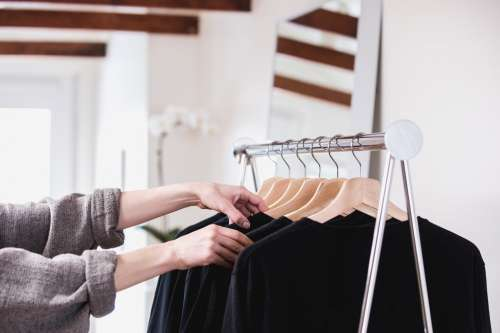 Comparing Black T-Shirts On A Clothing Rack In A Sun-Lit Shop Photo