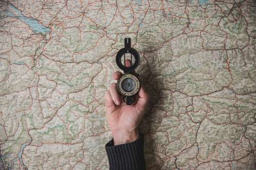Compass Held Above World Map Photo