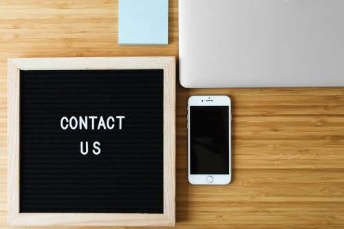 Contact Us Sign With Phone On Desk Photo