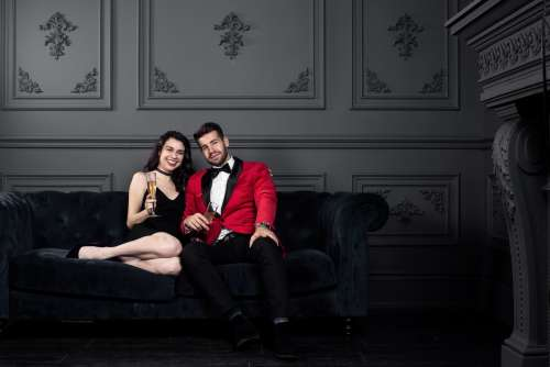 Couple In Formal Wear Cozy Up With Champagne Photo
