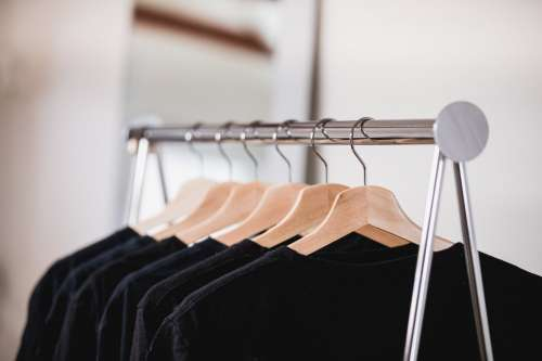 Dark Clothing On A Shop Rack With A Mirror In The Background Photo