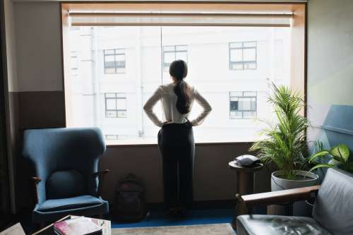 Female Executive Looks Out Modern Office Window Photo