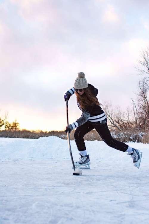 Female Hockey Player Practicing Stick Handling On Frozen Lake Photo