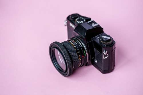 Film Camera On Pink Background Photo